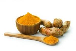 Bowl of turmeric powder and turmeric root