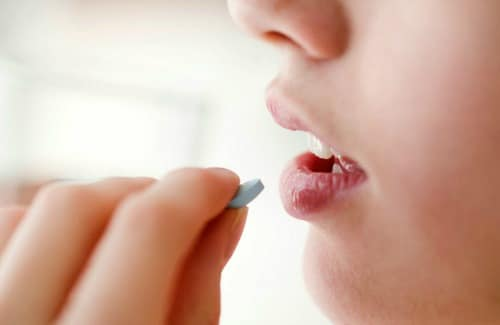 Woman taking an oral probiotic